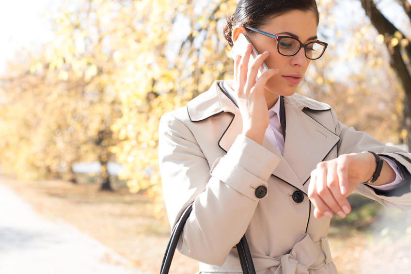 Businesswoman checking time while using cell phone at park