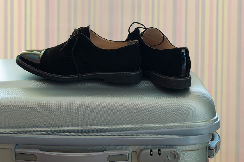 Suitcase with elegant black leather shoes on it