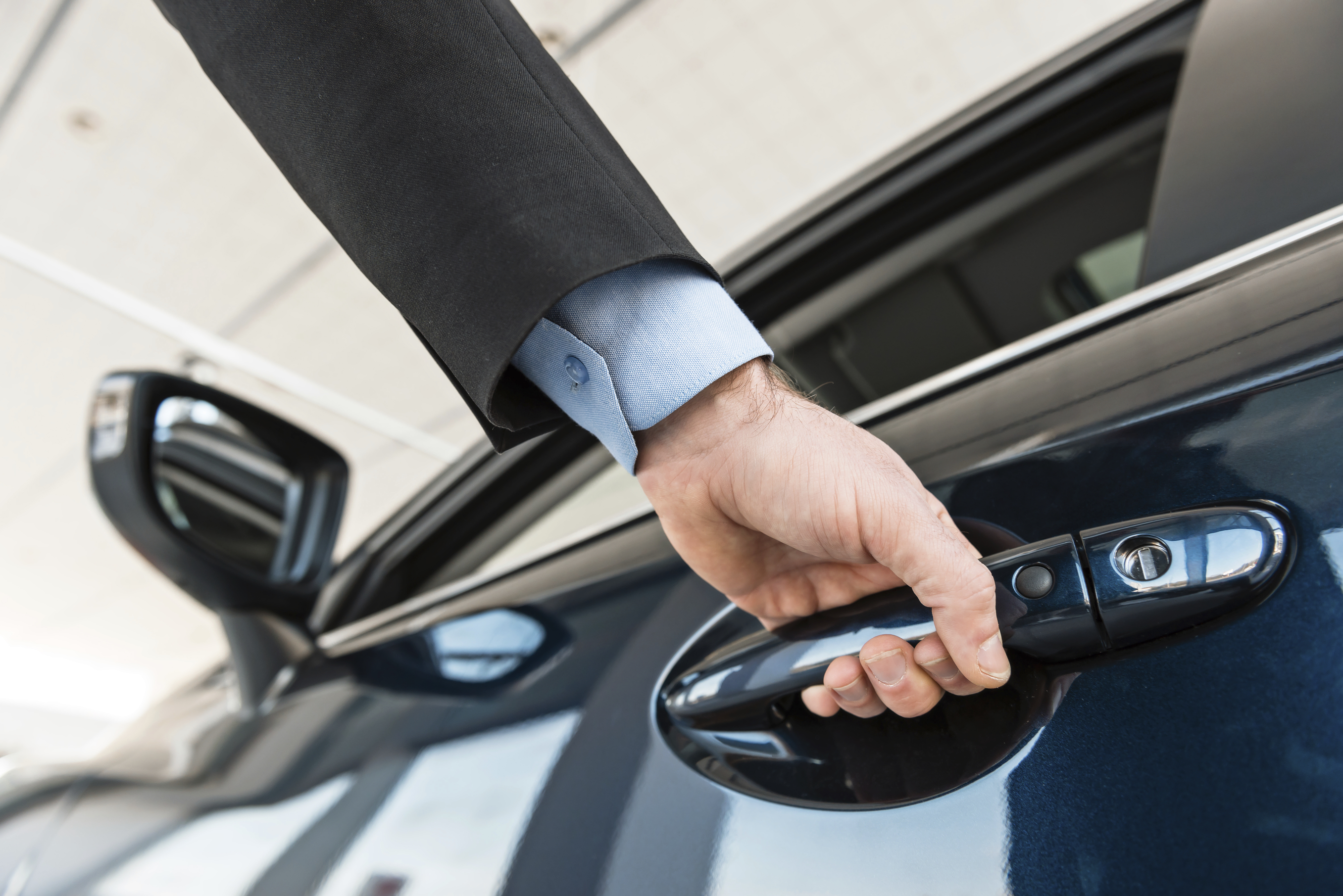 Close up photo of young man hand touching and openning new car. Concept for car rental